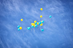 Yellow and blue balloons in the sky Royalty Free Stock Photos