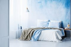 Yellow and blue bedding on white bed in minimal bedroom interior. With lamp on wooden table Stock Photos