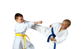 With yellow and blue belts sportsmen are doing paired exercises karate Stock Images