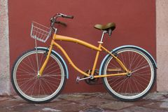 A Bicycle on a street over red wall Royalty Free Stock Image