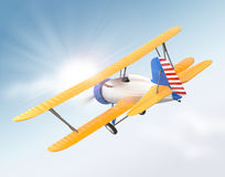 Yellow and blue biplane flying in the sky Stock Photo