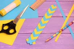 Yellow and blue bookmark made from folding paper. Scissors, glue stick, paper sheets, ruler, pencil on a table Royalty Free Stock Photo