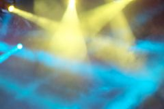 Yellow and blue concert lights shine through the smoke. Abstract beautiful background of bright multicolored rays of light. Blurry royalty free stock photography