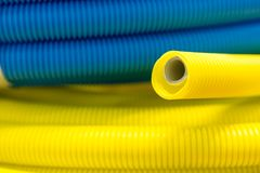 Yellow and blue corrugated plastic tube. Abstract industrial background Stock Image