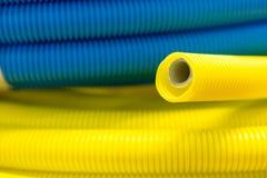 Yellow and blue corrugated plastic tube. Stock Image