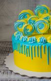 Yellow and blue cream cheese color drip cake with merengues Royalty Free Stock Images