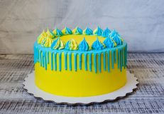 Yellow and blue cream cheese color drip cake with merengues Royalty Free Stock Image