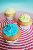 Yellow and blue cupcakes Stock Images