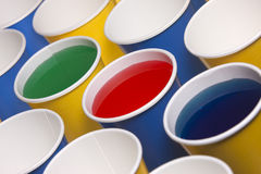 Yellow and blue cups with liquid. Stock Photos