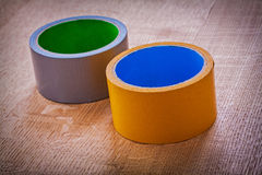 Yellow and blue duct tapes on vintage brown wood Stock Image