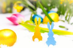 Yellow and blue easter bunny in the snow. Yellow and blue easter bunny and easter eggs in the snow Stock Photos