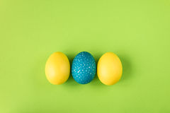Yellow and blue Easter egg on bright green background, top view Stock Photos