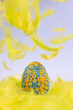 Yellow and blue Easter egg lying in yellow feathers, feathers fa Stock Photo