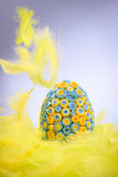 Yellow and blue Easter egg lying in yellow feathers, feathers fa Royalty Free Stock Photos