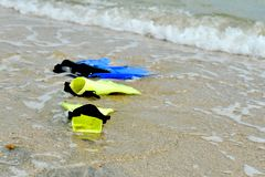 Yellow and blue flippers for diving lie on the beach in the water.  stock photo