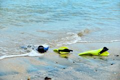 Yellow and blue flippers for diving lie on the beach in the water.  stock images
