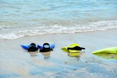 Yellow and blue flippers for diving lie on the beach in the water.  stock image