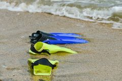 Yellow and blue flippers for diving lie on the beach in the water.  royalty free stock images