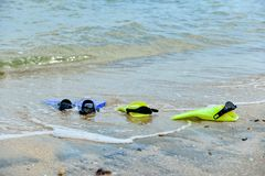 Yellow and blue flippers for diving lie on the beach in the water.  stock photography