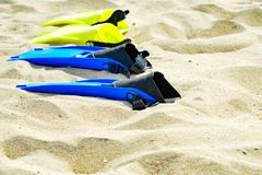 Yellow and blue flippers for diving lie on the sand in a row.  stock image