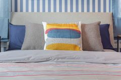 Yellow and blue graphic print pillow setting on stripe bedding. Bedroom stock photography