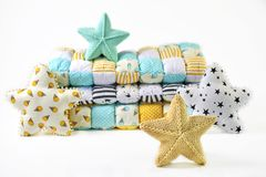 Yellow and blue-green knitted and stitched five-pointed star shaped pillows and patchwork comforter on white background.