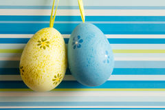 Yellow and blue hanged Easter eggs on striped background.  Stock Image