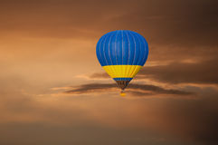 Yellow blue Hot Air Balloon in Flight on sunset Stock Photography