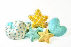 Yellow and blue knitted and stitched five-pointed star shaped pillow, patchwork comforter and heart shaped pillows on white backgr. Ound Stock Photos