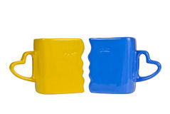 Yellow and blue mug. With the handle in the form of heart, isolated on a white background Stock Photos