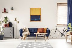 Yellow and blue painting hanging on white wall in bright living. Room interior with grey cupboard, gold lamp, sofa with blanket and pillows, and bike standing royalty free stock image