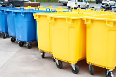 Yellow and blue plastic garbage cans on city street. Yellow and blue plastic garbage cans on the city street Royalty Free Stock Photos