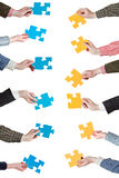 Yellow and blue puzzle pieces in people hands Stock Image