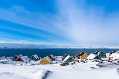 Yellow, blue, red and green inuit houses covered in snow at the Stock Photo