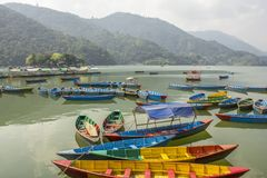 A yellow blue red green wooden boats on a lake against the backdrop of mountains royalty free stock photography