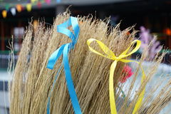 Yellow and blue ribbons tied in bows on a broom. Pancake, post, shrovetide Royalty Free Stock Photo