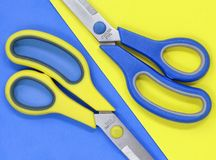Yellow and blue scissors, against a contrasting flat lay background royalty free stock images