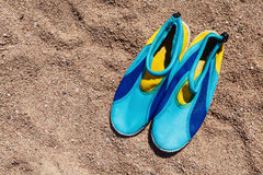 yellow-blue shoes that protect feet from the coral on the beach Stock Images