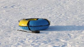 Yellow and blue snowtube is on white snow at winter day stock footage