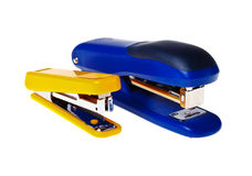 Yellow and blue staplers  (isolated). Yellow and blue staplers on a white background close-up (isolated Stock Photo