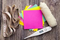 Yellow and blue sticky note with empty space for a text on wooden background. Health concept with thermometer bandage and metre royalty free stock photo