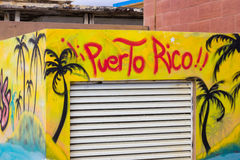 Yellow and blue street art depicting black palm trees with the words Puerto Rico spray painted on a square building Royalty Free Stock Photography