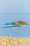 Yellow and blue sunshades on sandy beach against blue sky in Sithonia Royalty Free Stock Images
