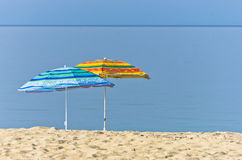 Yellow and blue sunshades on sandy beach against blue sky in Sithonia Stock Image