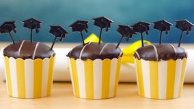 Yellow and blue theme graduation party cupcakes with cap hats toppers. Royalty Free Stock Photos