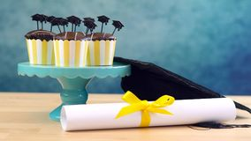 Yellow and blue theme graduation party cupcakes with cap hats toppers. Royalty Free Stock Photo