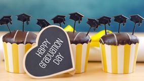 Yellow and blue theme graduation party cupcakes with cap hats toppers. Stock Image