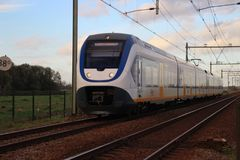 Yellow blue train type SLT sprinter of dutch Railways NS on the train bridge of Gouda in the Netherlands.  Royalty Free Stock Images