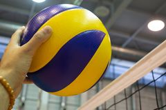 Yellow-blue volleyball on the floor in the gym. Volleyball spike hand block over the net. Yellow-blue volleyball on the floor in the gym stock images