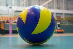 Yellow-blue volleyball on the floor in the gym. Team of athletes playing volleyball royalty free stock photography